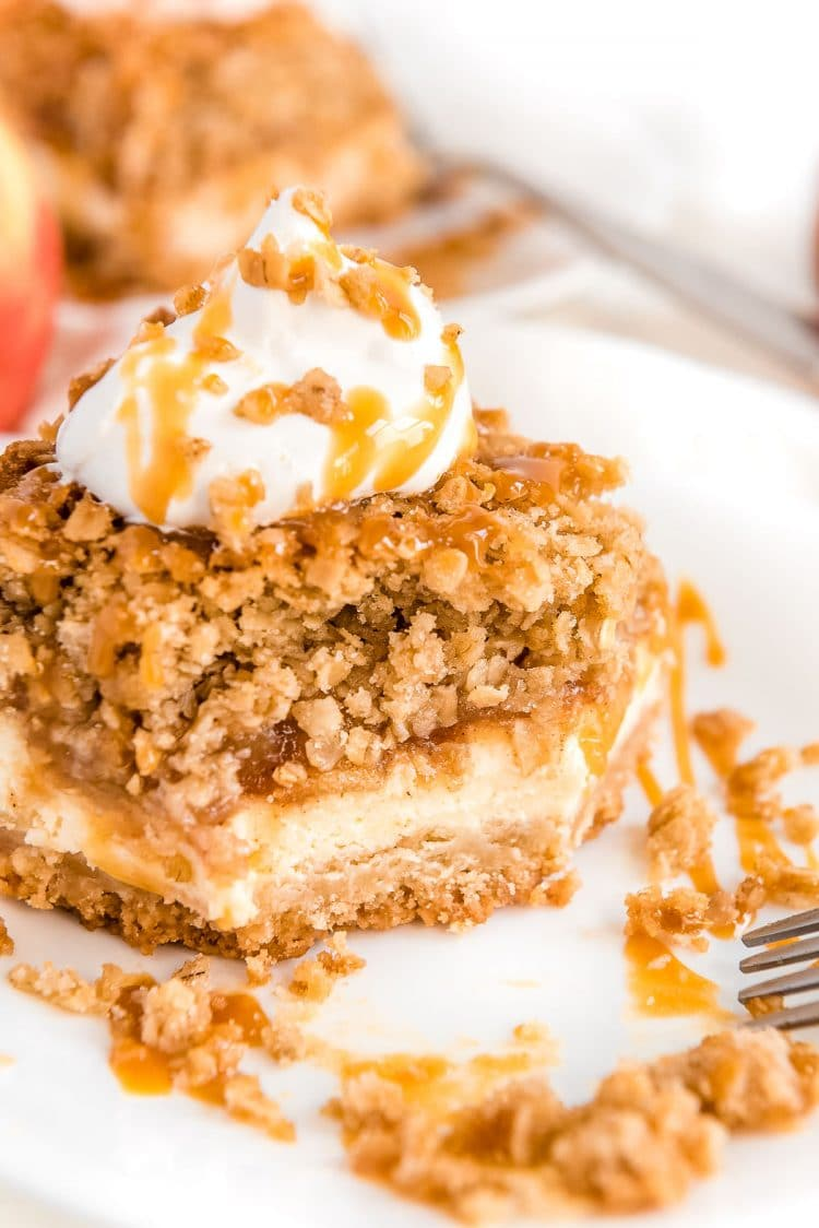 Slice of caramel apple cheesecake with a bite taken out of it.