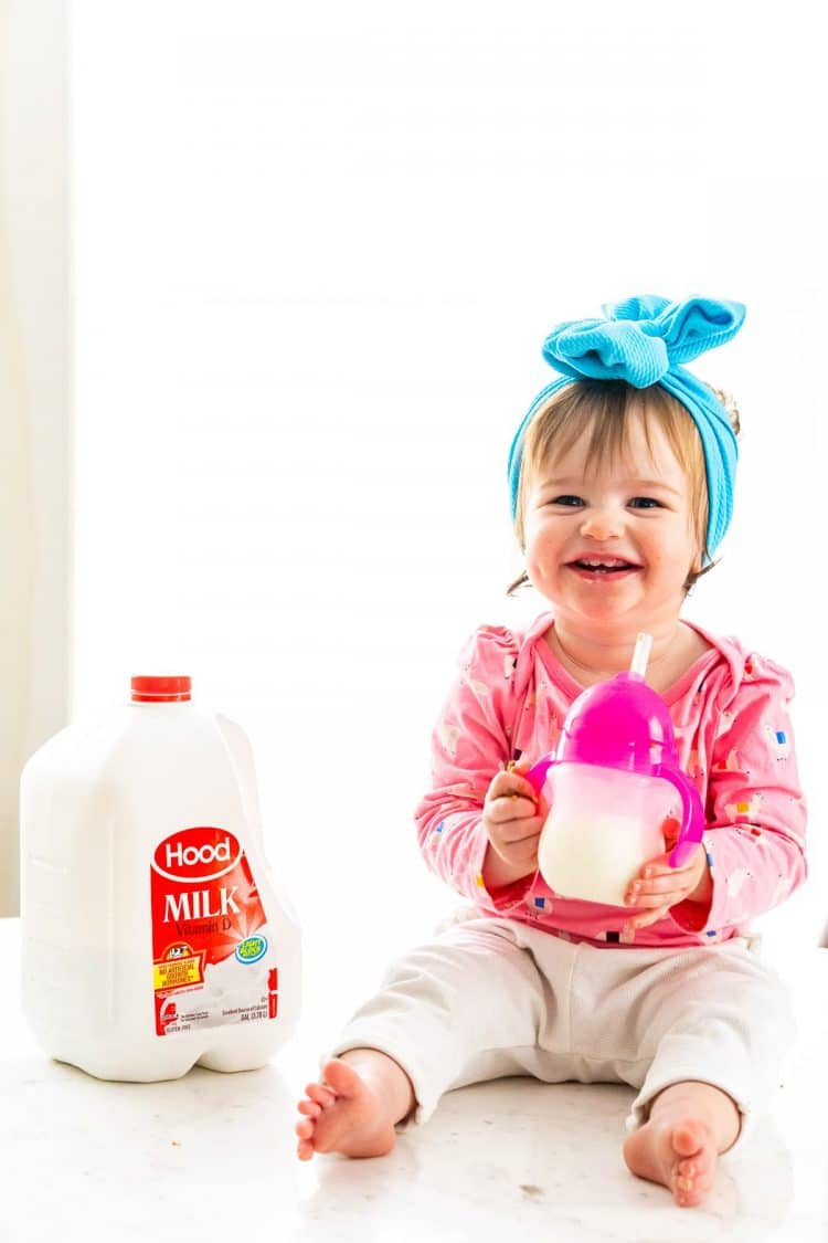 Baby girl sitting on a table drinking a sippy cup filled with milk.