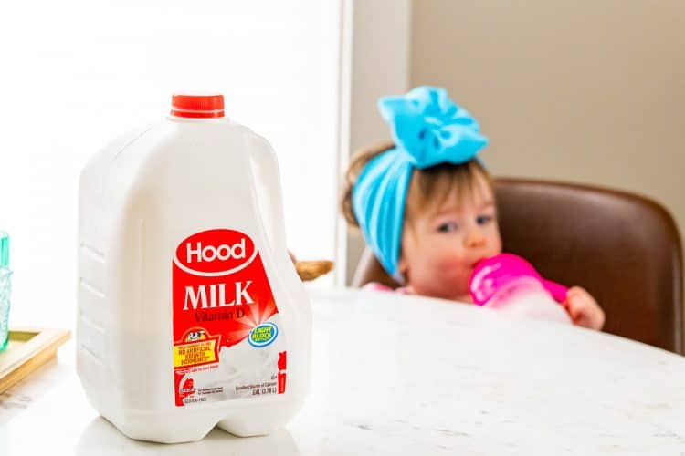 Gallon of milk on a table with a baby girl sitting in a chair in the background.