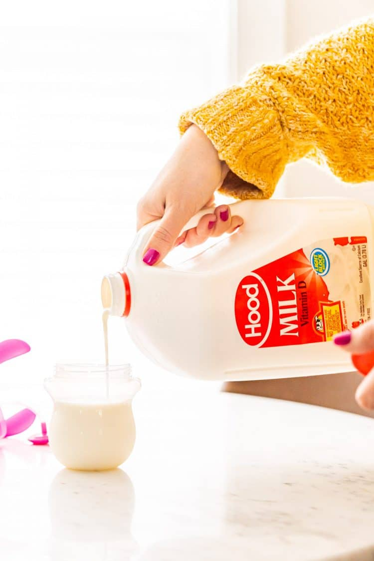 Woman in a yellow sweater pouring milk into a sippy cup.