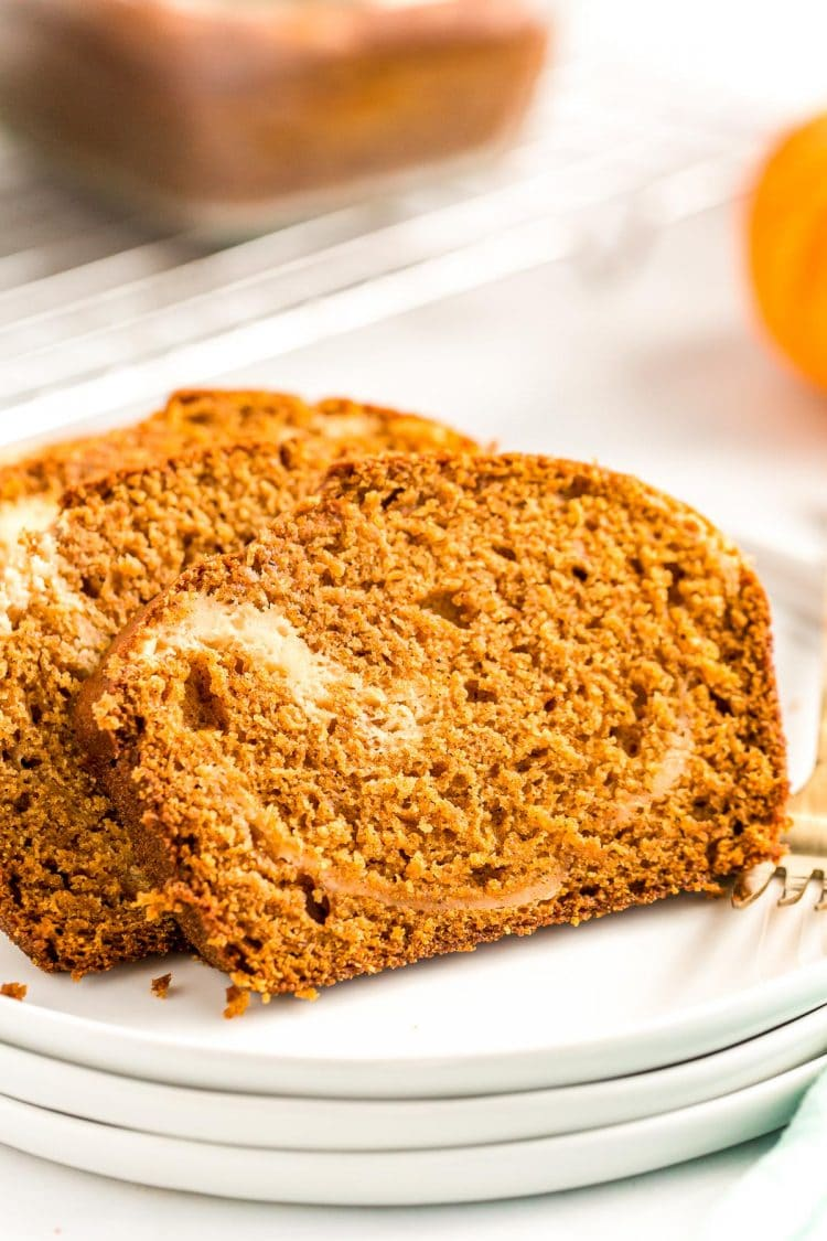 Close up photo of two slices of pumpkin bread with a cream cheese swirl on a white plate.