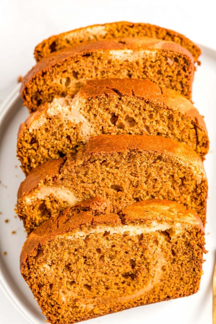 Slices of pumpkin cream cheese bread on a white plate.