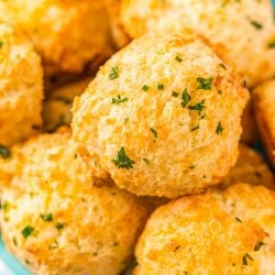Close up photo of a bowl of cheddar drop biscuits topped with herbs.