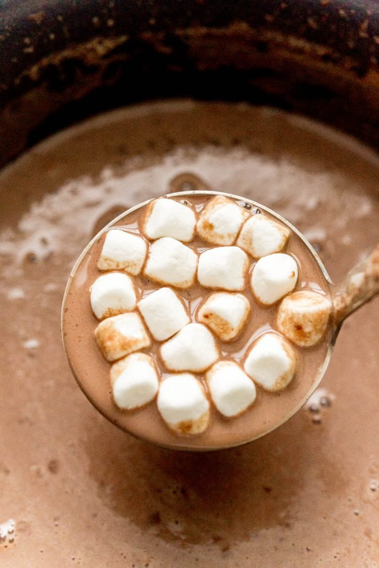 A ladle lifting hot chocolate and marshmallows out of a crockpot.
