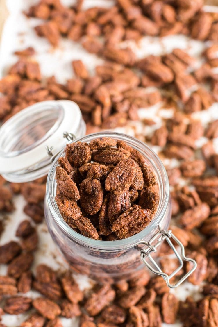 Candied pecans in a glass jar with pecans scattered around.