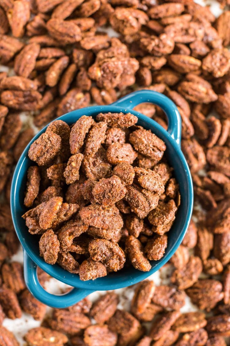 overhead photo of a blue bowl with candied pecans in it and scattered around.