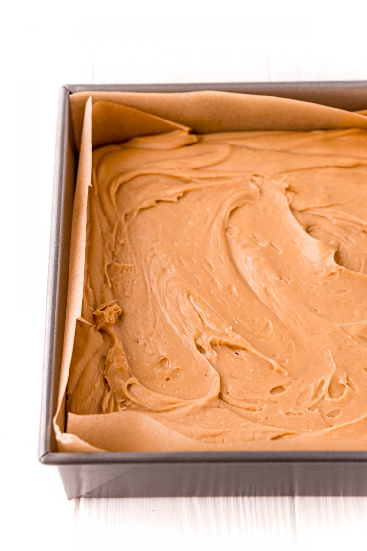 Peanut butter fudge in a baking dish lined with parchment paper.