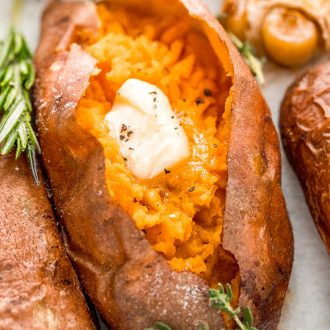 Close up photo of a baked sweet potato with garnishes around it.