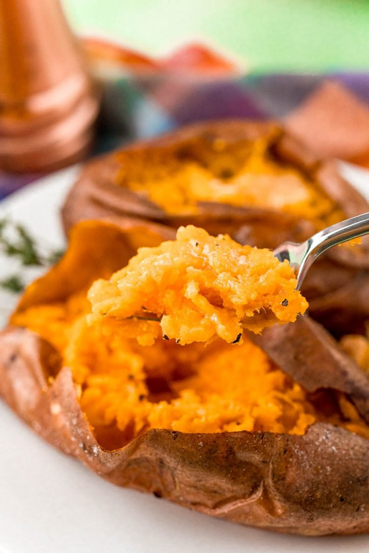 A fork full of baked sweet potato.