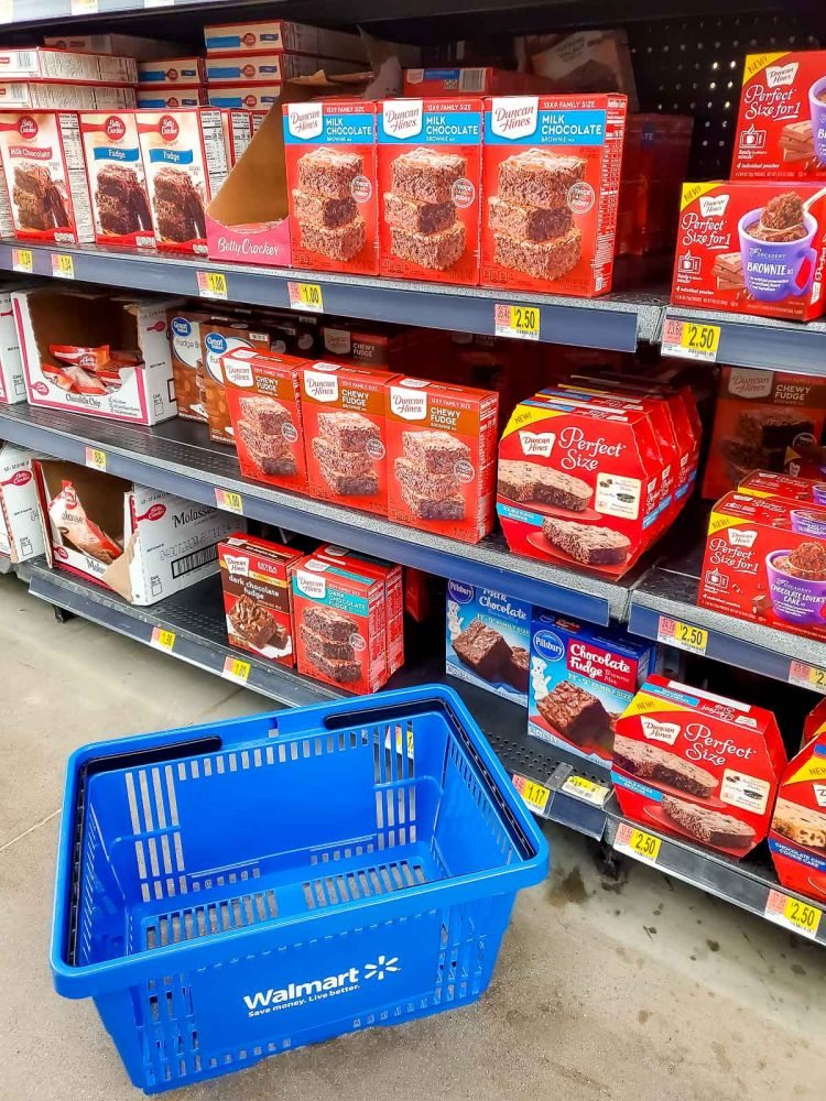 Baking aisle with a Walmart shopping basket on the floor.