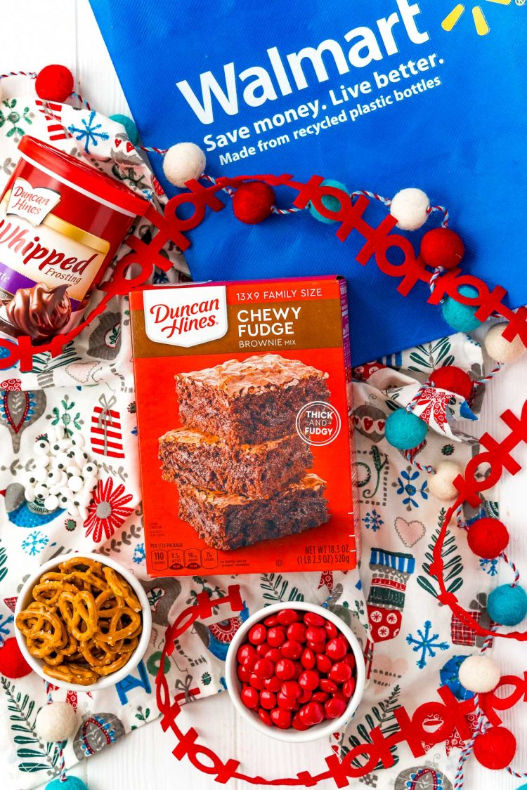 A box of Duncan Hines Brownie Mix and other baking ingredients on a table with a Walmart reusable bag.