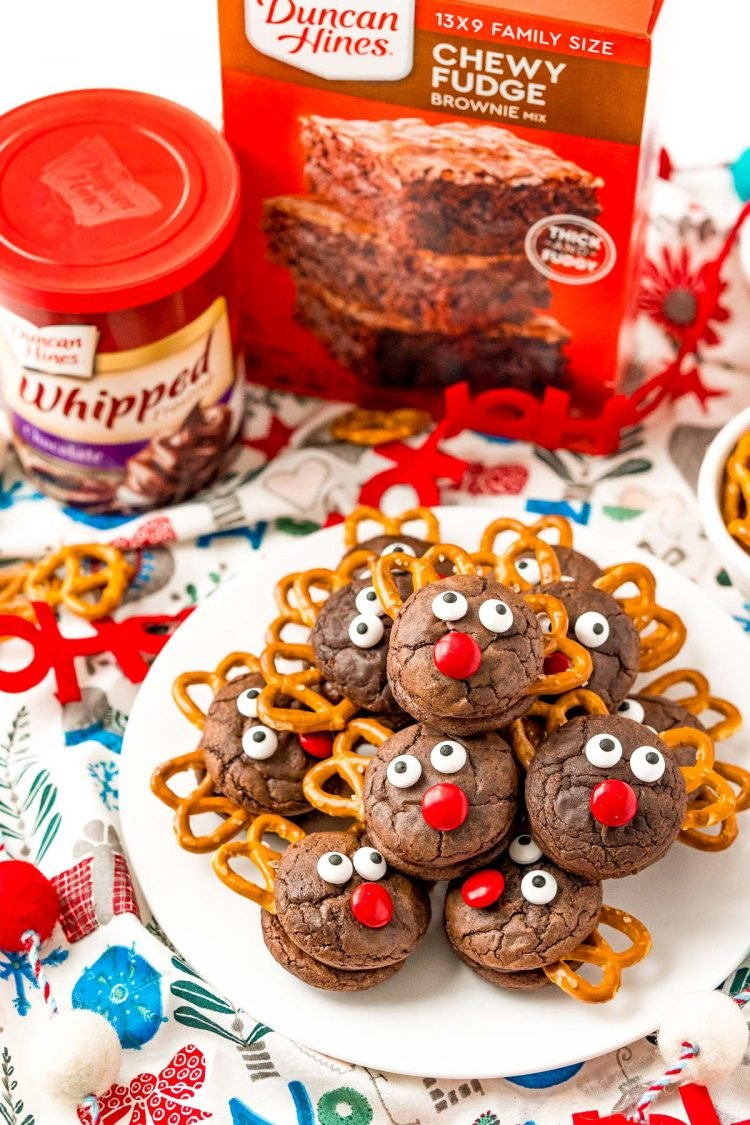 A plate of reindeer cookies with brownies mix and frosting in the background.