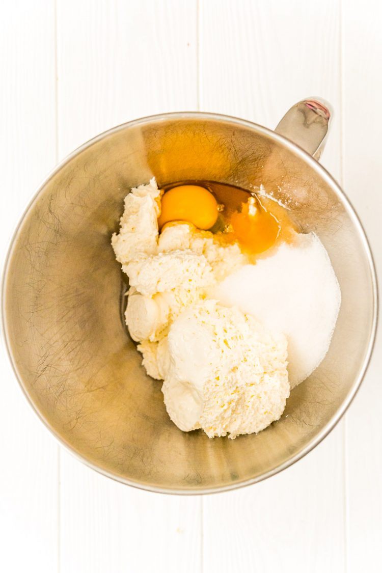 Ingredients to make a cheesecake filling in a mixing bowl.