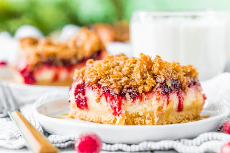 Close up photo of cranberry cheesecake bars with a bite taken out of it.