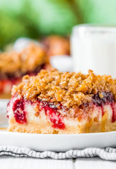 Close up photo of a slice of cranberry cheesecake bars on a small white plate.