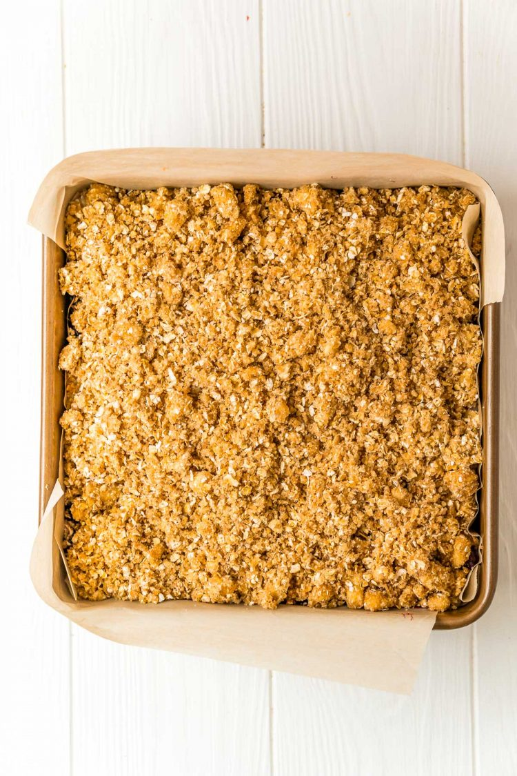 Oatmeal crumble topping on top of a cheesecake in a square baking dish.