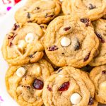 A white plate filled with cookies with white chocolate chips and craisins.