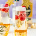 Close up photo of a champagne flute filled with a cocktail and raspberries.
