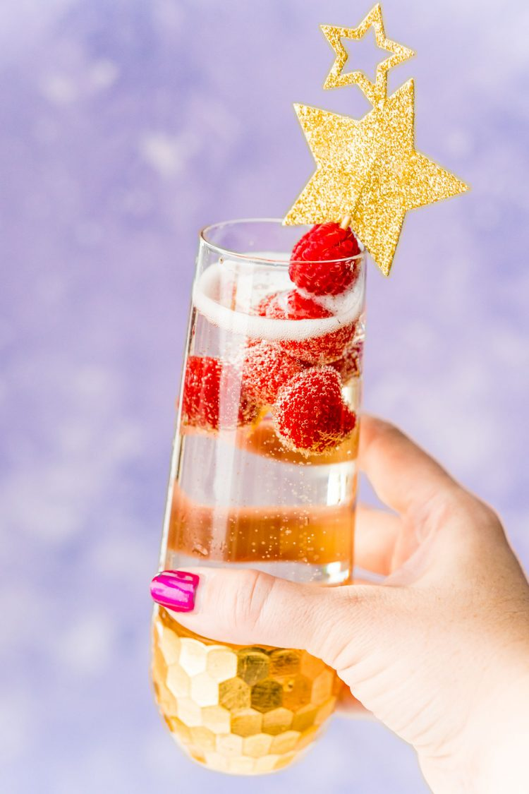 Woman's hand holding up a champagne cocktail with raspberry garnish.