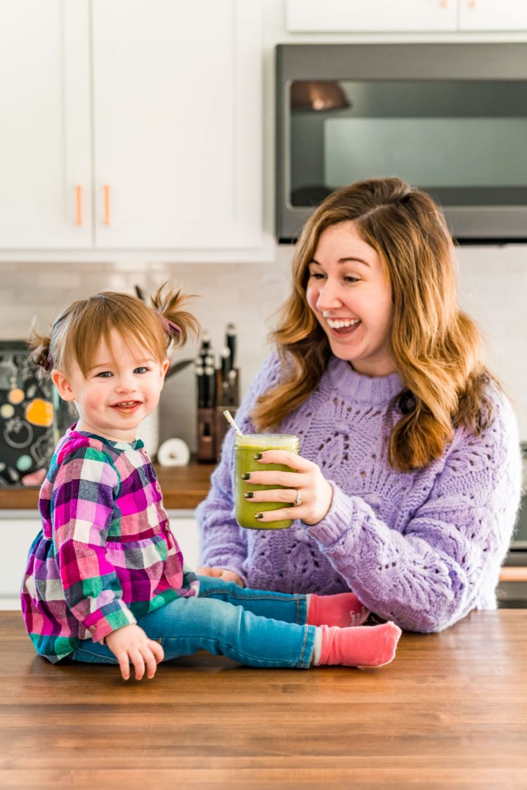 Toddler girl and her mother sharing a smoothie in the kitchen.