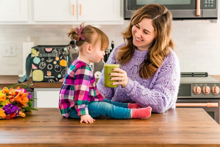 Mother and daughter in a kitchen drinking a smoothie.