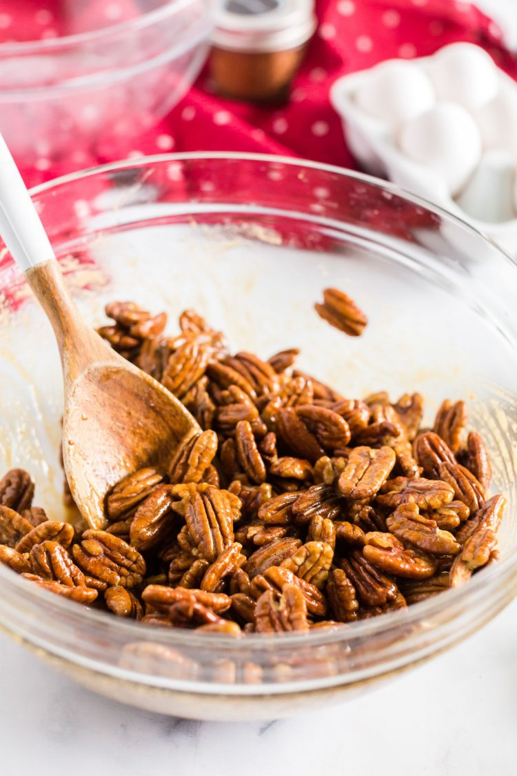 pecans in a mixing bowl with a wooden spoon.