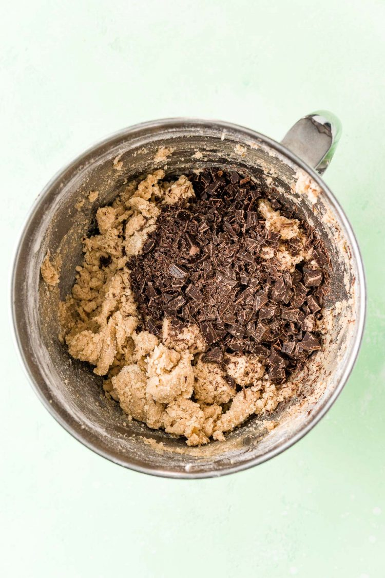 Overhead photo of a mixing bowl filled with cookie dough and chocolate chunks ready to be mixed in.