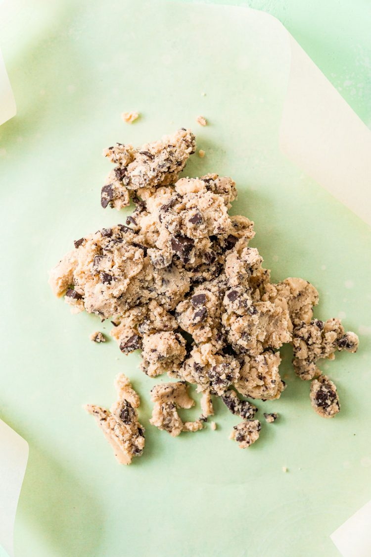 Crumbly cookie dough on parchment paper.