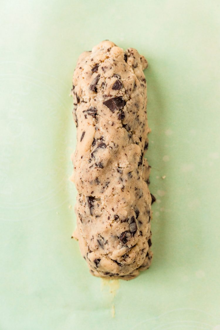 Chocolate chunk cookie dough formed into a log on parchment paper.