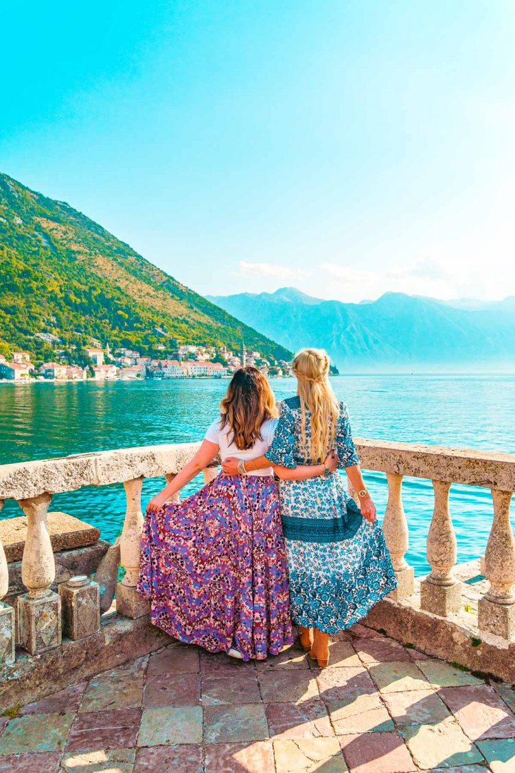 Two woman at Lady Of The Rocks in Perast, Montenegro looking out over the balcony in the cove.