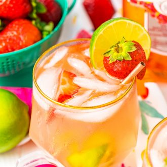 Close up photo of a pink gin spritz in a gold rimmed glass garnished with a lime and strawberry.