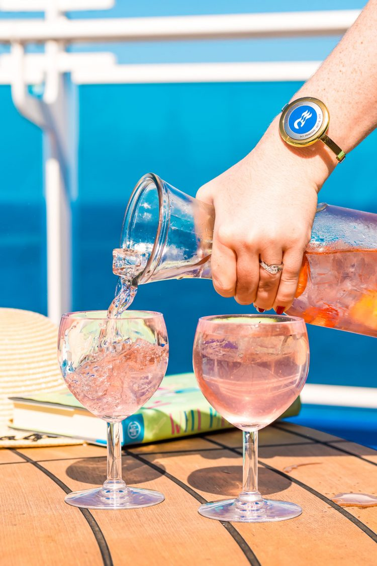 Woman pouring a cocktail out of a carafe into wine glasses on the deck of a cruise ship.