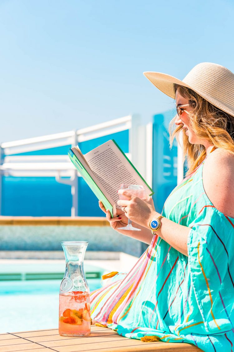 Woman drinking a fruity cocktail and reading a book near the pool on a cruise ship.