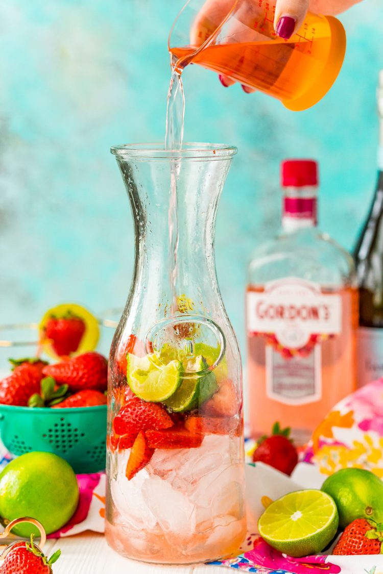 Pink liquor being poured into a carafe with strawberries and limes.