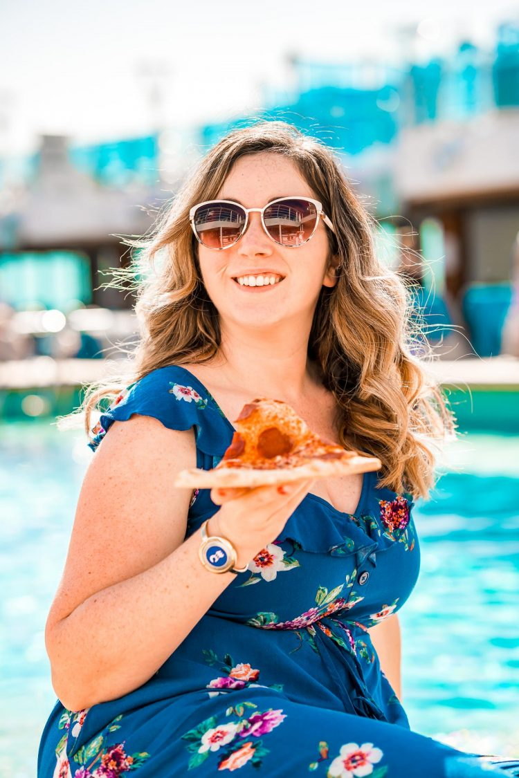 Woman sitting with a slice of pizza by the pool on a princess cruise ship.