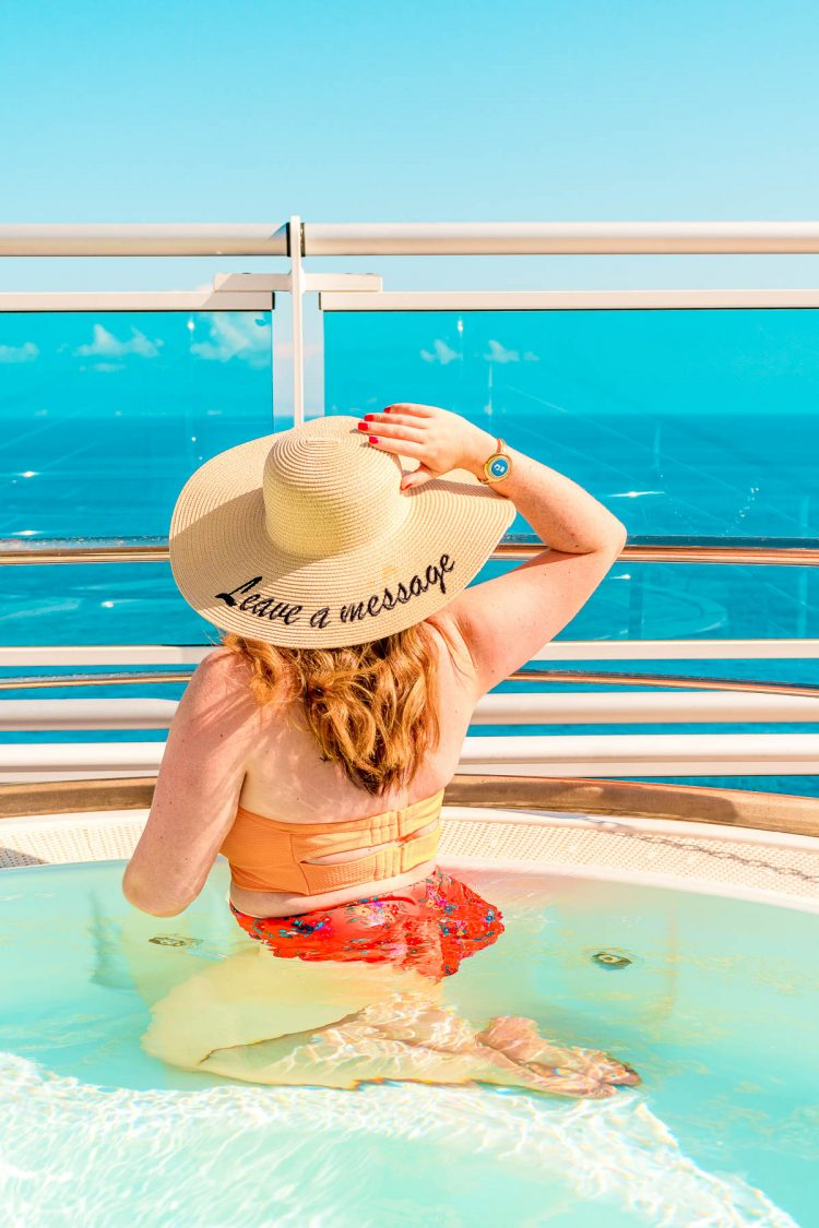Woman sitting in a hot tub looking out over the water on a cruise ship.
