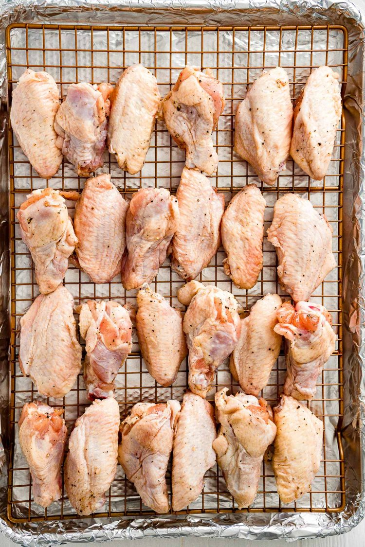 Uncooked chicken wings arranged on a wire rack on a baking sheet.