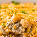 Close up photo of a serving spoon scooping tater tot hotdish out of a casserole dish.