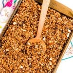 Homemade granola on a sheet pan with a wooden spoon scooping it.