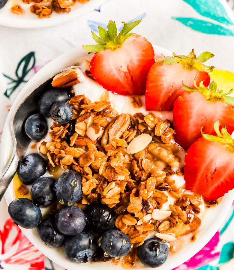 Close up photo of a bowl of yogurt topped with blueberries, granola, and strawberries.