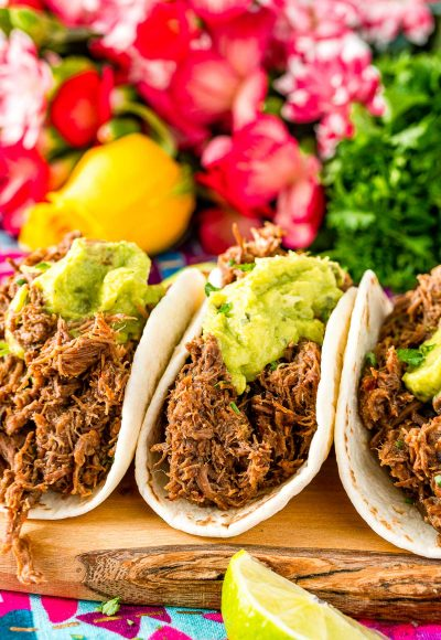 Close up photo of three barbacoa tacos on a cutting board with pink flowers in the background.