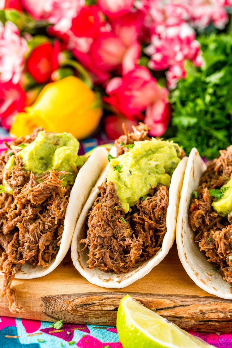 Close up photo of tacos made with barbacoa beef and topped with guacamole. Pink flowers in the background.