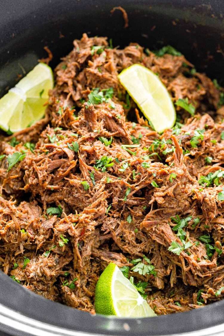 Close up photo of shredded barbacoa beef in a crockpot garnished with cilantro and lime wedges.