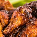 Close up photo of chicken wings with a sticky sauce on them.