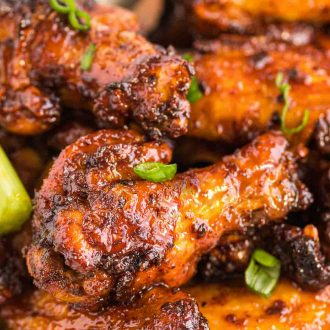 Close up photo of chicken wings coated in a sticky sauce and topped with scallions.