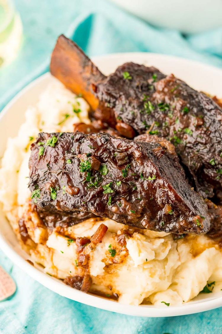 Braised beef short ribs served over a bowl of mashed potatoes.