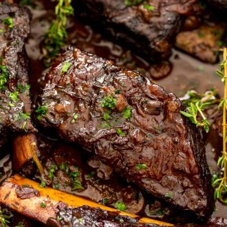 Braised beef short ribs in a pan with sauce.