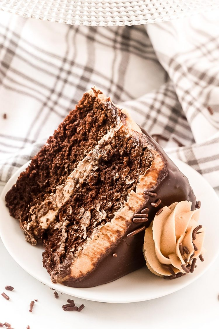 A slice of chocolate cake with cookie butter frosting laying on a white plate.