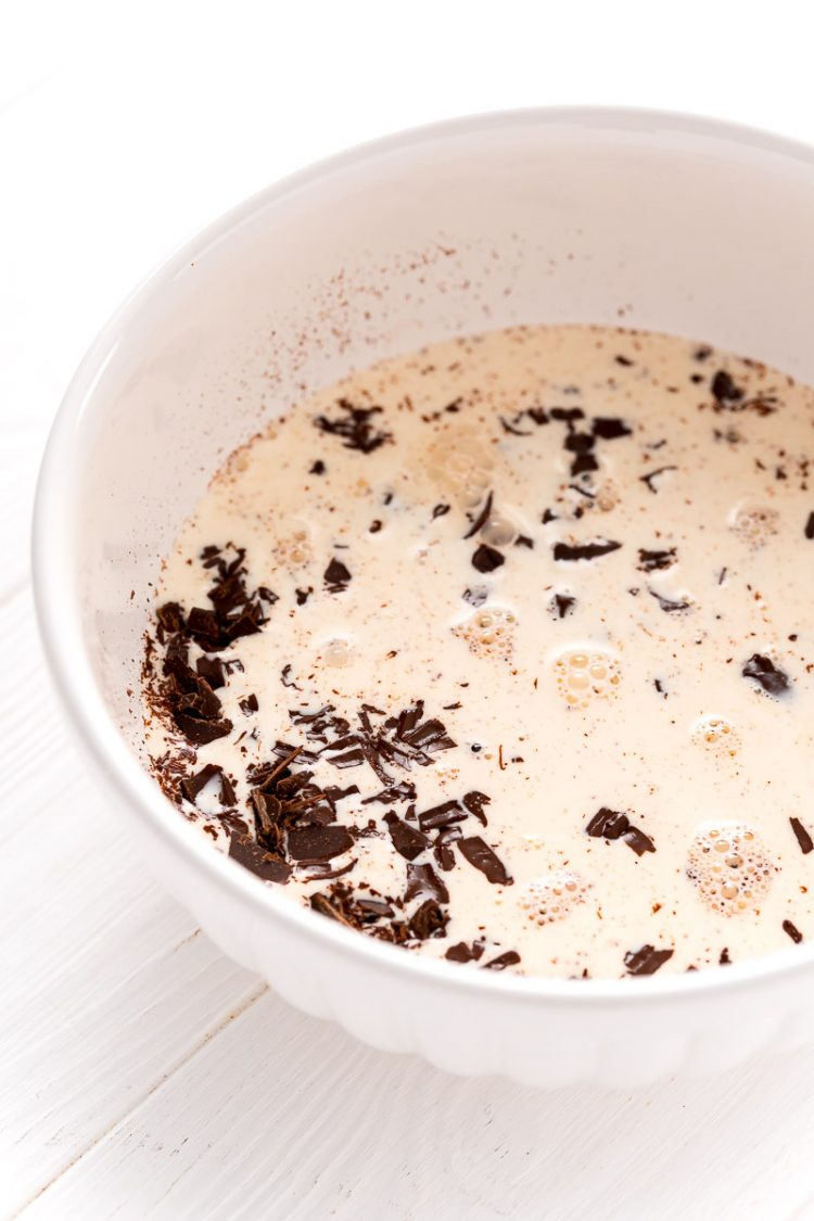 White bowl filled with chopped chocolate and heavy cream.
