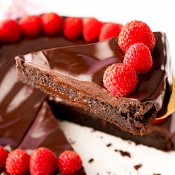 Close up photo of a slice of flourless chocolate cake topped with ganache and fresh raspberries being lifted with a serving spatula from the rest of the cake.